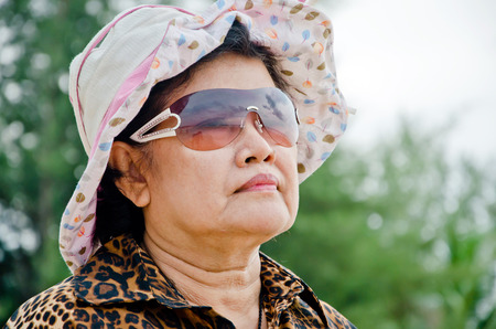 an older people wear pink hat and look ahead photo