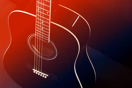 Black acoustic guitar, red-blue toned photo.