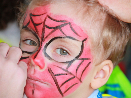 face painting: Beautiful blond hair little boy with face painting of spiderman