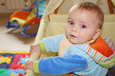 romper: Beautiful baby with a colored romper standing suite in His cot Stock Photo