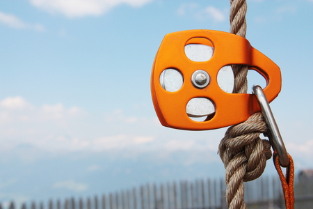karabiner: Orange Climbing Pulley with rope and carabiner Stock Photo