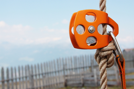 carabiner: Orange Climbing Pulley with rope and carabiner Stock Photo