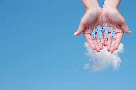 Paper family in hands on blue sky background concept welfare