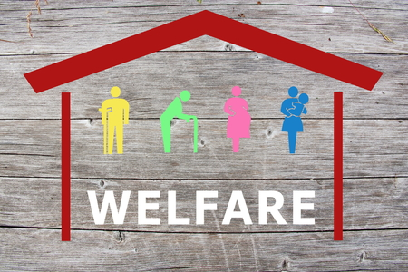 Welfare concept on wooden background with colored home and old man, disabled, pregnant and woman with baby Stock Photo