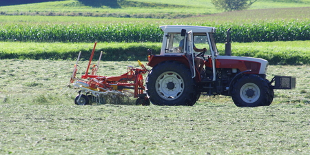 grass cutting: Tractor with hay tedder working on a mountain field Stock Photo