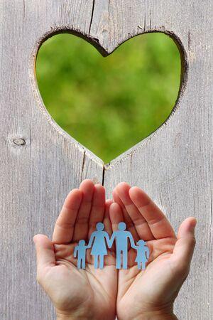 紙の家族の手の心と木製の背景