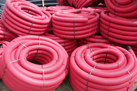 Red corrugated plastic pipes used for underground electrical lines Reklamní fotografie - 84519370
