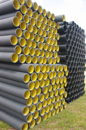 Stack of black corrugated plastic pipes Stock Photo