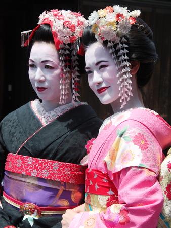 JAPAN, KYOTO - MAY 17, 2016: Beautiful Young and Mature Geisha walking in Kyoto old town Geisha district Japan. Editöryel