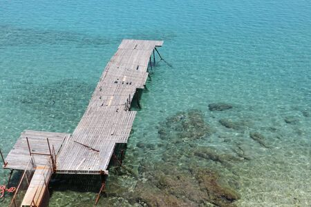 Old wooden pier on a greek turquoise sea