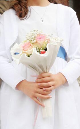 Młoda dziewczyna trzyma w dłoniach bukiet kwiatów pierwszej komunii