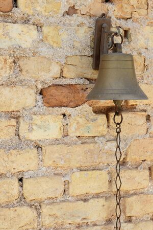 Small bronze bell fixed to a bricks wall