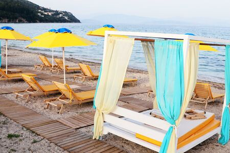 Yellow beach umbrella with foldable cots and wooden boardwalk 写真素材