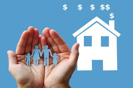 Paper family in hands with white home on blue background welfare concept 写真素材