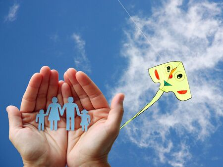 Paper family in blue sky background with colorful kite 写真素材