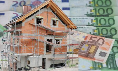 House under construction with Euro banknotes in the background 写真素材
