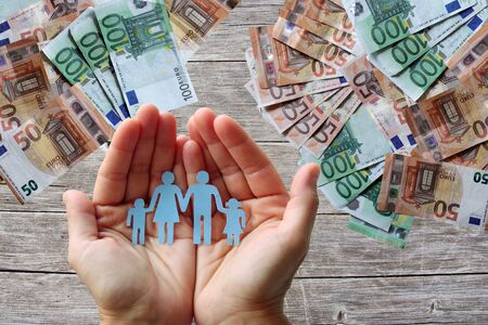 Paper family in hands on wooden background with euro banknotes