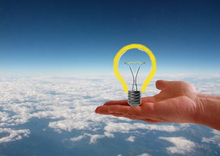 Light bulb in hand on aerial sky view background