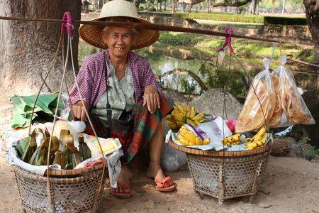 THAILAND, SUKHOTHAI - DECEMBER 17 2008: Aged Thai woman peddler hawker selling fresh fruit near the ruins of the ancient city Sukhothai