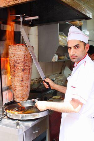 TURKEY, ISTANBUL - MAY 18 2011: Man slicing turkish doner kebab kebap in Istanbul Turkey. 報道画像