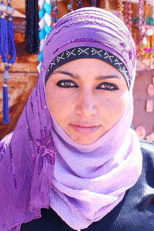 JORDAN, PETRA - FEBRUARY 06, 2009: Mysterious young Jordanian woman wearing a violet veil over her hair.