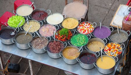 Group of metal pots on a street stall containing various kinds of colorful sweet soups What hem Hue Vietnam 写真素材
