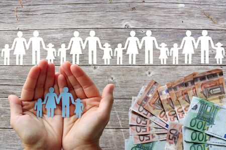 Paper family in hands with wooden background and white banknotes