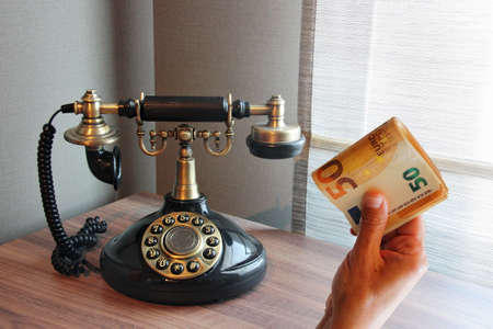 Old vintage telephone on a desk with money in hand