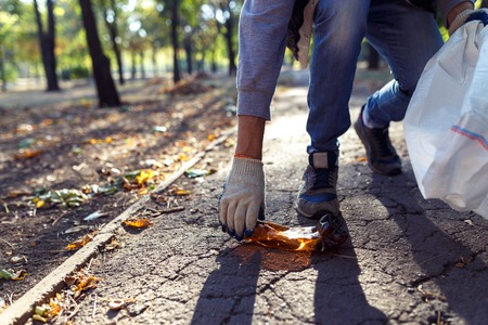 young man picking up trash outdoor. close up