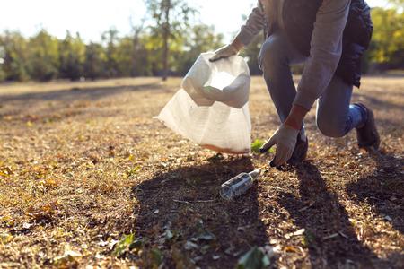 Jeune homme ramassant des ordures à l'extérieur. fermer Banque d'images - 71637438
