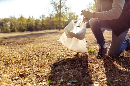 altruismo: Joven recogiendo basura al aire libre. de cerca Foto de archivo