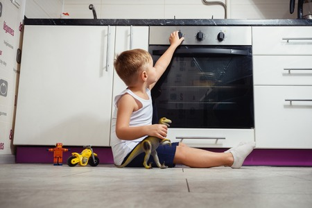 accident prevention. The child unattended playing in the kitchen with a gas stove. without retouch 版權商用圖片