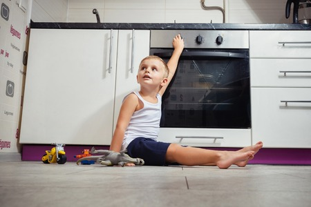accident prevention. The child unattended playing in the kitchen with a gas stove. without retouch Stock fotó
