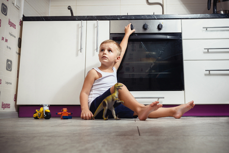 accident prevention. The child unattended playing in the kitchen with a gas stove. without retouch Stock Photo