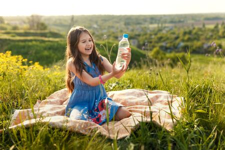 girl in grass with plastic bottle with water shows gesture by finger