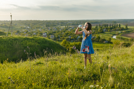 little girl drinks mineral water on the nature