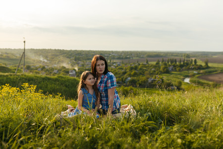 Little cute girl with her mother sitting at sunset in summer Banco de Imagens