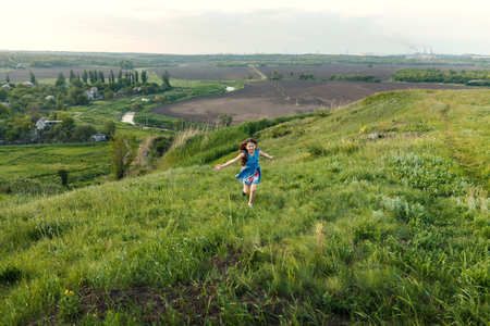 Little girl running on meadow with sunset Banco de Imagens