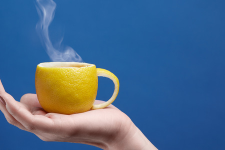 A tea cup made of lemon. Lemon cup in hand on a blue background. Creative composition on theme of natural fruit tea Banco de Imagens