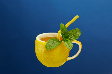 A cup of tea made from natural lemon with mint leaves. Creative composition on the theme of natural tea