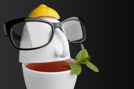 Creative composition on the theme of tea. Tea cups in the form of a human face with glasses