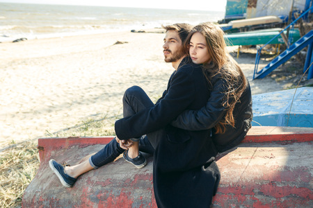 Happy young couple spending time on the sea shore in spring