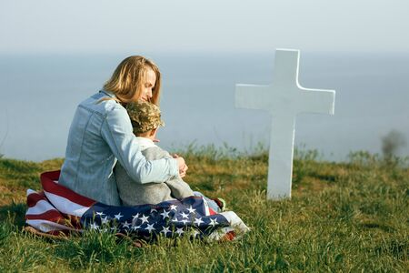 Mom and son are sitting on the grave of a soldier. Mom brought her son to the grave of his father on memorial day 27 may