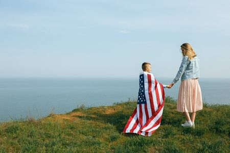 single mother with son on independence day of USA. Woman and her child walk with the USA flag on the ocean coast. Wonam dressed in a coral dress with a denim jacket.