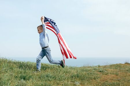A little boy runs with the flag of the United States. July 4th Independence Day.