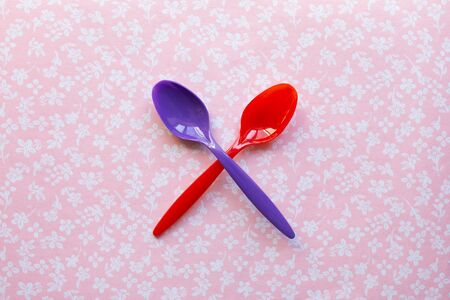 two plastic spoons for children on a fabric background