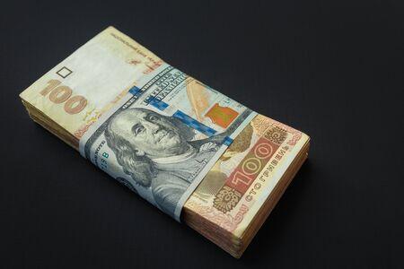 Value of Ukrainian hryvnia and American dollars. A pack of Ukrainian hryvnia wrapped one hundred dollar bill 写真素材 - 142147703