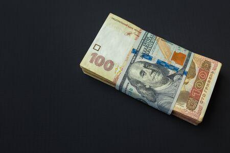 Value of Ukrainian hryvnia and American dollars. A pack of Ukrainian hryvnia wrapped one hundred dollar bill 写真素材 - 142147382