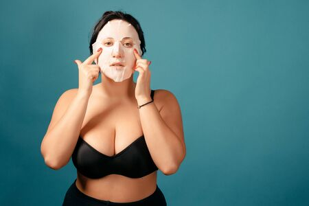 Happy plus size girl doing full split. Happy body positive concept. I love my body. Attractive overweight woman with white moisturizing mask