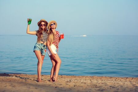 two European girls have fun in the summer on the beach